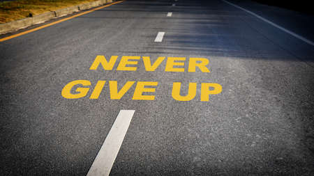 Never give up word on asphalt road surface with marking lines. Sustainable economic success concept and business positive challenge emotion idea