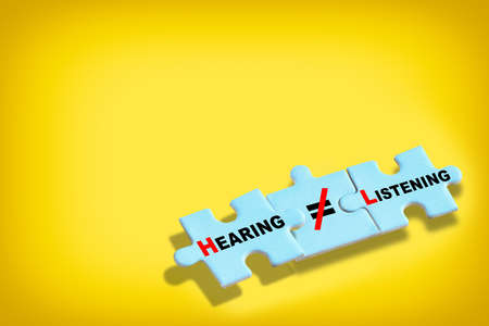 Hearing is not same as listening written on blue puzzle isolated on yellow background. Business leadership concept and teamwork to communication idea