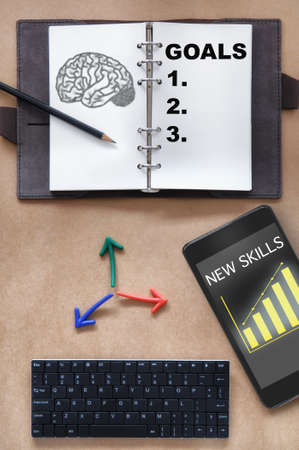 Top view of brain drawing and goals written on organizer book with pencil, colorful arrow, new skills and growth graph on smartphone and mini keyboard on working desk. Reskilling and upskilling machine learning concept