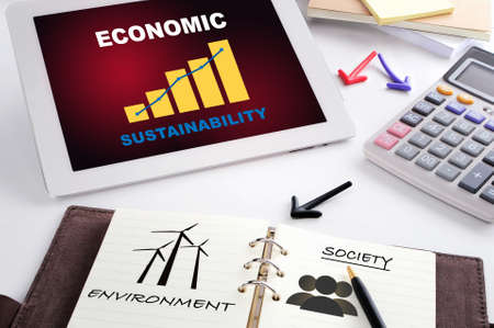 Sustainable E-commerce with growth graph on computer digital tablet  and wind turbine environment and society drawing on book. Long term business success responsible concept and online selling idea