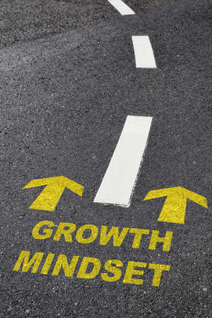 Growth mindset with yellow arrow marking on road surface with white marking line. Optimism empathy personality concept and motivation to success idea Reklamní fotografie