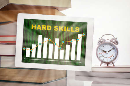 Hard skills and financial growth graph trading on digital computer tablet with stack of textbook and time to change words on alarm clock isolated on white background. Skill sets teachable ability idea