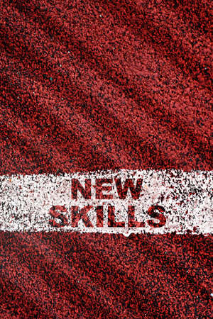 New skills written on red sport track with starting line. Future ahead reskilling and upskilling concept and self development idea