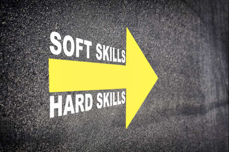 Soft skills and hard skills words with yellow arrow marking on road surface. Business success with direction concept and intelligence emotional quotient idea Standard-Bild