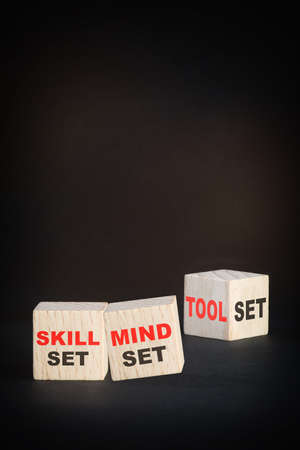 Skill set, mindset and tool set written on wooden cubes on black background. Empower yourself concept and beginning to success idea