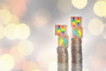 Rainbow model on wooden cube on stack of coins on bokeh background. Making money with saving concept and trading return on investment roi idea Standard-Bild
