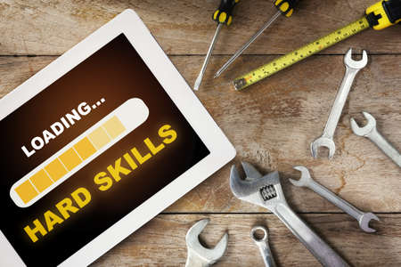 Hard skills loading on computer digital tablet with tools supplies on wooden background. Expertise challenge concept and business success idea