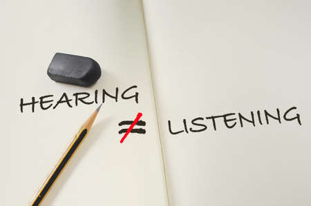 Hearing not equal listening written on book with pencil and eraser. Communication with understanding empathy concept and soft skill idea Standard-Bild