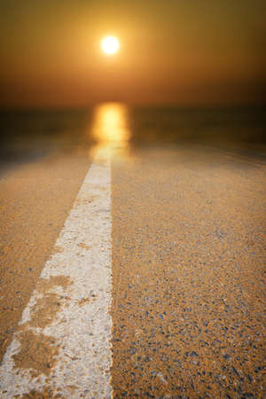 Asphalt road surface with white marking line leading into abstract blur sunlight and sun. Transportation concept and journey road trip idea Standard-Bild