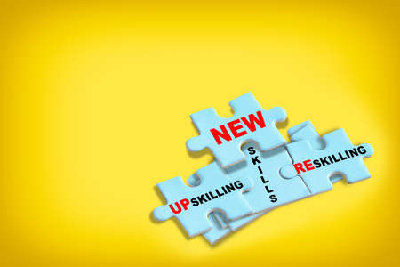 Reskilling, up skilling and new skills written on blue puzzle isolated on yellow background. Optimism and empathy personality concept with creativity idea