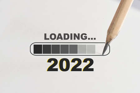 New year 2022 loading written on white paper with processing symbol and pencil. Beginning to success concept and challenge idea