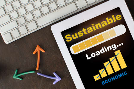 Business sustainable strategy loading with economic growth graph on computer digital tablet with arrow and keyboard  on desk. Return on investment roi concept and trading with responsibility idea Standard-Bild