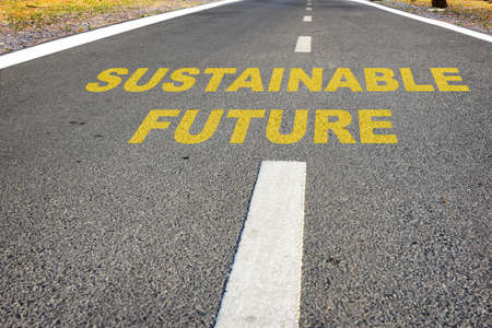 Sustainable future word on asphalt road surface with marking lines. Inspiration and motivation concept and effort idea