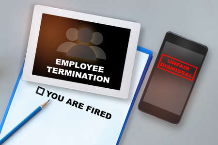 Employee termination words on computer tablet and unfair dismissal on smartphone on working desk. Technology disruption concept and economic recession with fired idea