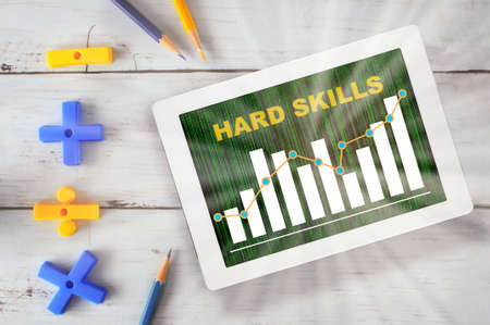 Hard skill and growth graph loading on computer digital tablet with mathematics symbol and colored pencil on wooden desk Standard-Bild