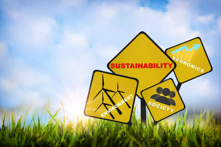 Environment, society and economics written on yellow sign on grasses on sky background. Renewable clean energy investment for sustainability concept and alternative energy idea