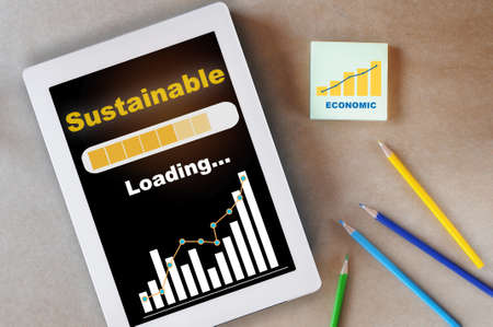 Sustainable E-commerce loading on computer digital tablet with growth graph on desk. Long term business success concept and selling online idea