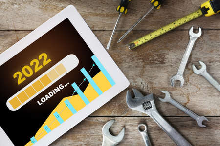 New year 2022 business sustainability and growth graph loading on computer digital tablet with tools supplies on wooden background. Sustainable future to success concept and challenge idea Standard-Bild