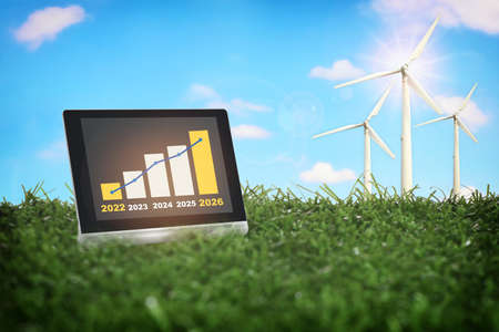 2022 to 2026 sustainable business strategy and financial growth graph stock trading on computer digital tablet with wind turbine on green grasses. Smart technology concept and responsibility idea Standard-Bild