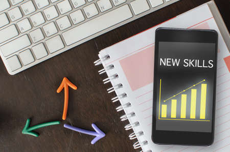 New skills and economic growth graph on smartphone on book with arrow and keyboard on desk. Online education concept and sustainable business strategy idea