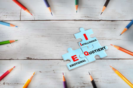 Emotional quotient and intelligence written on blue puzzle jigsaw with shadow on wooden background. EQ and IQ formula for success concept