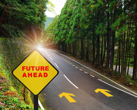Future ahead written on yellow sign on highway road and white marking lines in the forest. Business recovery concept and challenge to success idea Standard-Bild