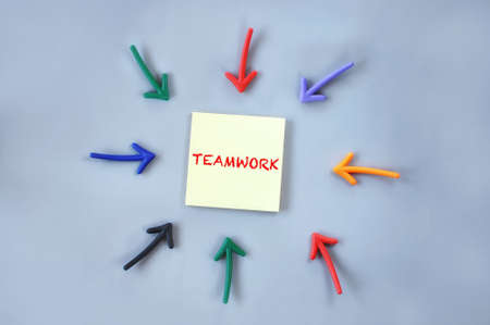 Teamwork written on yellow sticky note with colorful arrow on grey background. Business synergy concept and communication idea