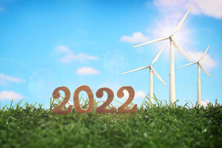 New year 2022 with wind turbine on green grasses on fluffy cloud background. Clean energy to sustainable future environment concept and alternative energy economic growth idea Standard-Bild