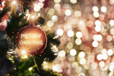 Merry christmas word on red ball decoration on christmas tree on abstract bokeh blurred background. Happiness festive party concept Standard-Bild
