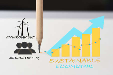 Drawing sustainable business strategy concept and future ahead idea. Economics growth graph, wind turbine environment and society written on white paper with pencil