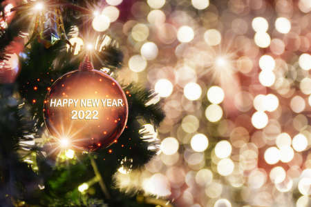 Happy new year 2022 word on red ball decoration on christmas tree on abstract bokeh blurred background. Happiness festive party concept