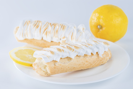eclair: delicious eclair on a plate and lemon Stock Photo