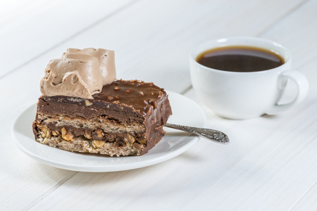 piece of chocolate cake and cup of coffee on a background of white painted wood Stock Photo