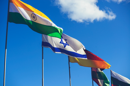 International summit. Flags of different countries blowing in the wind on the sky background