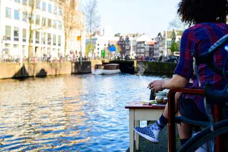 Unidentified hippy person smoking cannabis joint and enjoying the view of the river Amstel in Amsterdam