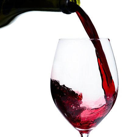 Alcoholic drink. Pouring expensive red wine from bottle into the wineglass isolated on white background
