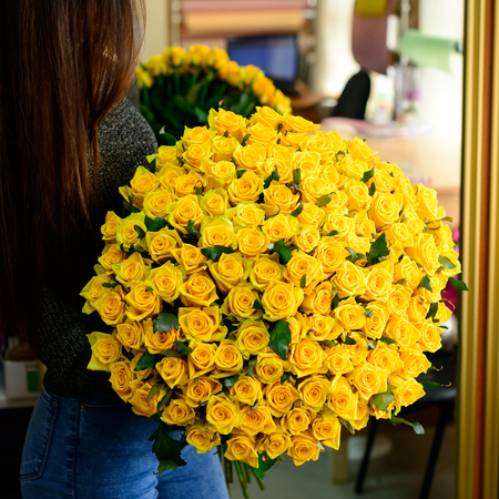 Happy brunette girl received big bouquet of beautiful fresh yellow roses