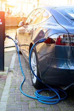Laden des modernen Elektroautos auf der Straße in den Sonnenstrahlen. Wiederaufladbare Fahrzeugbatterien, Zukunft des Transports