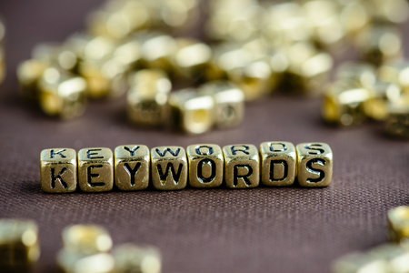 Word KEYWORD made from small golden letters on the brown backgro Stock Photo