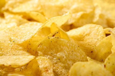 Food background of delicious chips. Corrugated golden chips pota