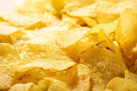 Food background of delicious chips. Corrugated golden chips pota Reklamní fotografie