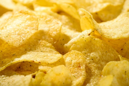 Food background of delicious chips. Corrugated golden chips pota Stock Photo