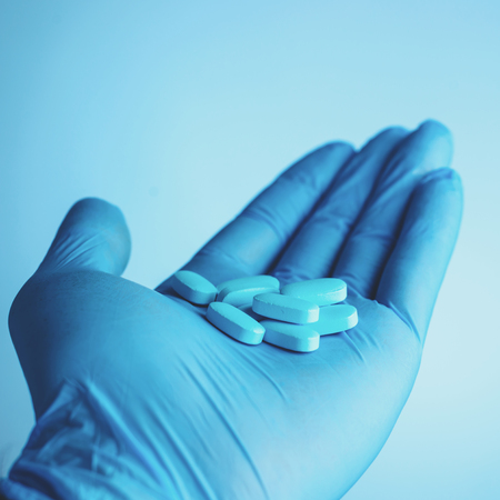 Blue pills in doctors hand on blue background. Life save service Stock Photo