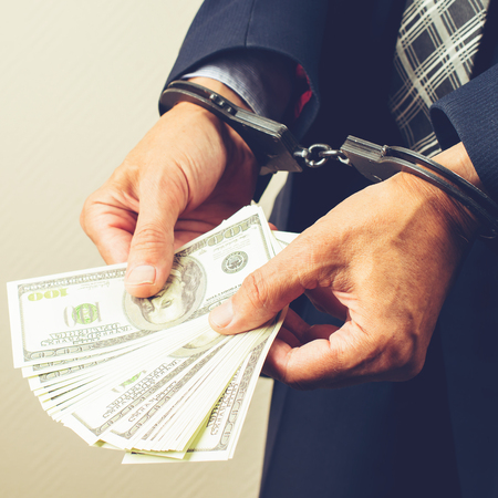 arrested official in handcuffs counting dollar banknotes. Concep