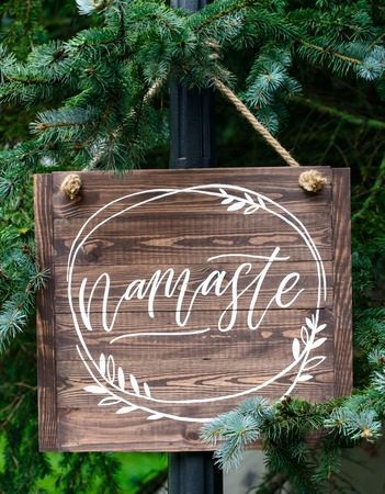 written word namaste of wooden signboard