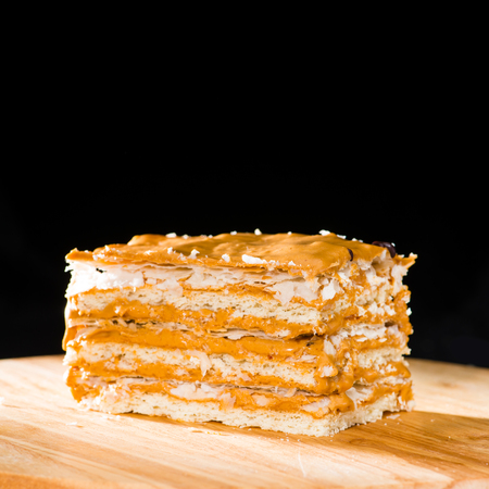 close-up delicious cake of puff pastry with sour cream on a wood