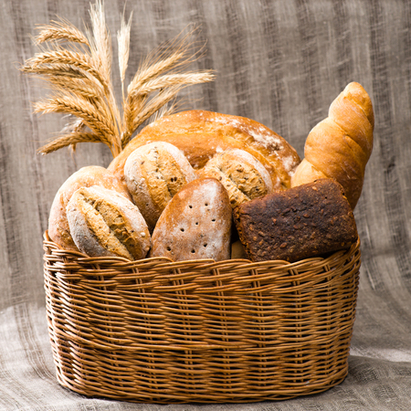 various types of fresh bread in a basket, textile background. Ru Banco de Imagens