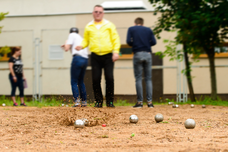 man throwing metal ball for petanque game on sand