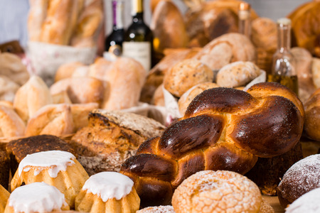 various types of fresh bread in a table: rum baba, challah, whea Stock Photo