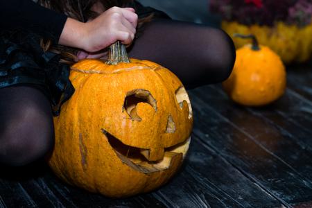 girl sitting near the Halloween pumpkin head jack lantern on dar